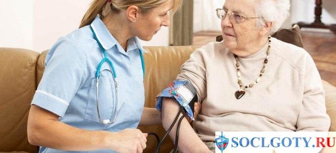 врач измеряет давление гипертонику-инвалиду